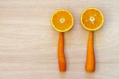 2 halfs апельсина и 2 морковей на деревянном текстурированном backgr Стоковые Фото