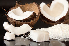Halfs of coconut, pieces of coconat, coconut flakes on black bac. Kground. Healthy food concept Royalty Free Stock Images