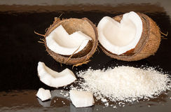Halfs of coconut, pieces of coconat, coconut flakes on black bac. Kground. Healthy food concept Stock Photos