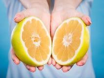 Halfs de citrinos amarelos da toranja nas mãos humanas Imagem de Stock