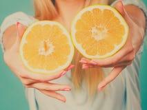 Halfs de citrinos amarelos da toranja nas mãos humanas Fotos de Stock