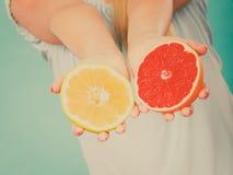 Halfs de citrinos vermelhos amarelos da toranja nas mãos humanas Fotos de Stock Royalty Free