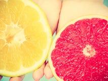 Halfs de citrinos vermelhos amarelos da toranja nas mãos humanas Fotografia de Stock