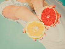 Halfs de los agrios rojos amarillos del pomelo en manos humanas Fotografía de archivo
