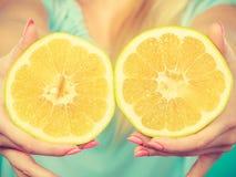 Halfs degli agrumi gialli del pompelmo in mani umane Fotografie Stock Libere da Diritti