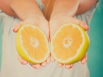 Halfs degli agrumi gialli del pompelmo in mani umane Fotografia Stock