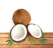 Halfs della noce di cocco sulle foglie verdi sulla tavola di legno sopra bianco Immagine Stock