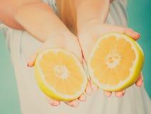 Halfs des agrumes jaunes de pamplemousse dans des mains humaines Image stock