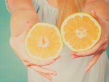 Halfs des agrumes jaunes de pamplemousse dans des mains humaines Image libre de droits