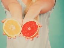 Halfs des agrumes rouges jaunes de pamplemousse dans des mains humaines Photographie stock libre de droits