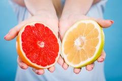 Halfs des agrumes rouges jaunes de pamplemousse dans des mains humaines Image stock