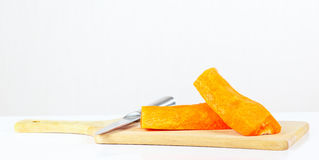 Halfs of fresh raw carrot with a knife on a cutting board. Closeup Stock Image
