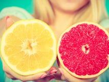 Halfs van gele rode grapefruitcitrusvruchten in menselijke handen Stock Foto's