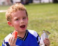 Halftime. Young sweaty boy having halftime snack of watermelon and juice Royalty Free Stock Photo
