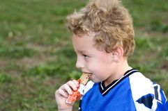 Halftime Snack. Soccer player eating halftime granola bar as snack Royalty Free Stock Photos