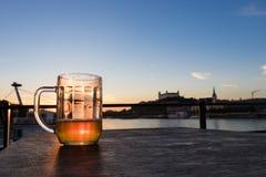 Halfvol glas bier op houten lijst aangaande het kasteel achtergrond van Bratislava, Slowakije stock foto