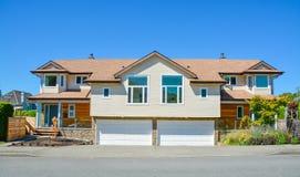 Halfvrijstaand huis voor twee families met brede garagedeuren langs de weg in de voorzijde stock afbeelding