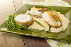 Halibut with asparagus risotto on green plate Stock Photos