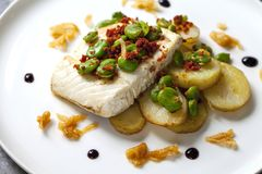 Halibut with baby potatoes, broad beans and chorizo. Baked halibut with baby potatoes, broad beans and chorizo Royalty Free Stock Photos