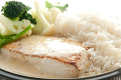 Halibut fillet with rice and cream sauce. Pan seared halibut fillet with cream and lemon glaze, served with lemon rice and fresh vegetables Royalty Free Stock Images