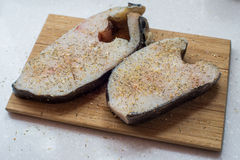 Halibut fish steak on a chopping Board Royalty Free Stock Image