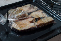Halibut fish steak in the package for baking on a baking sheet Stock Photography