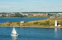 Sailboat sailing into Halifax Harbour. Single white sailboat passes lighthouse on way to Halifax in distance on brilliant blue water glistening in sunlight Royalty Free Stock Photos