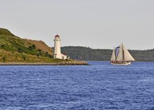 Halifax sailing. Sailboat passes lighthouse on George's island in Halifax Royalty Free Stock Photography