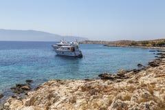 Yacht anchored near rocky coast Stock Photo