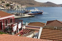 Tourists wait the ferry Dodekanisos Seaways on the way in Halki harbor, Dodecanese Islands, Greece. Halki island, Greece - August 27, 2018. Tourists wait the stock photo