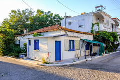 Halkidiki, Greece - JULY 12, 2016: Facade of a very small white house with blue windows in Halkidiki, Greece. Facade of a very small white house with blue Stock Photo