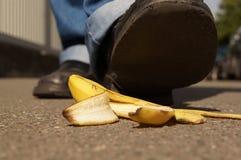 Halkning på en bananpeel Arkivfoto