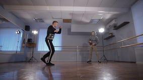 Hall для танцев репетиций 2 молодых танцора Молодой парень в черной куртке работает движения более низкого пролома акции видеоматериалы