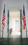 Hall with American Flags. A hall leading to a doorway outside has two American flags standing at its sides stock images