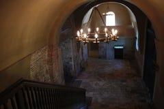 Hall av den forntida byggnaden med den träräcke, järnljuskronan och väggar för röd tegelsten arkivbilder