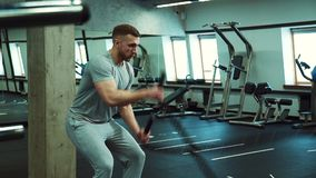 In the hall for crossfit a strong man pulls two ropes simultaneously. In gym bearded male athlete makes a physical effort to develop endurance stock footage