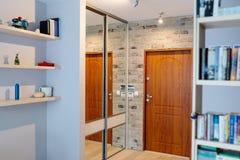 Hall de entrada en el apartamento moderno con el guardarropa del espejo foto de archivo