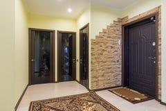Hall de entrada espacioso en el apartamento, tres puertas al cuarto, cuarto de baño y retrete foto de archivo libre de regalías