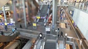 Hall de gare ferroviaire occupé, foule marchant les escaliers, trains arrivant sur la plate-forme banque de vidéos