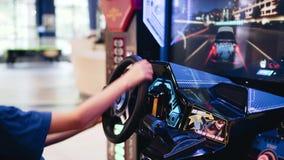 Hall des machines ? sous Le garçon joue un simulateur de voiture Il s'assied dans le siege du pilote banque de vidéos