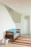 Hall with divan and striped rug. Interior of a modern house, hall with divan and striped rug stock image