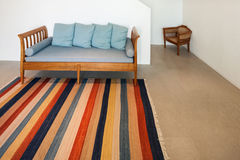 Hall with divan and striped rug. Interior of a modern house, hall with divan and striped rug stock photography