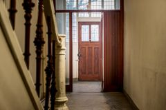 Hall entrance in a old and dark house. With wooden door and stairs stock image