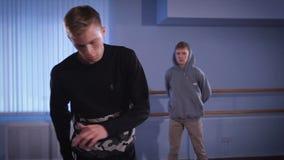 Hall för repetitiondanser Två unga dansare Den unga grabben i ett svart omslag arbetar förehavanden av det lägre avbrottet stock video