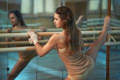 In  hall girl doing stretching near Barre Stock Photography