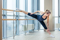 In the hall girl doing stretching near Barre.  Royalty Free Stock Image
