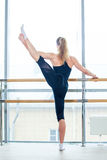 In the hall girl doing stretching near Barre Royalty Free Stock Photography