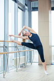 In the hall girl doing stretching near Barre Stock Photography