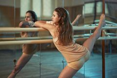 In  hall girl doing stretching near Barre Stock Photos