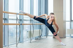 In the hall girl doing stretching near Barre Royalty Free Stock Photo